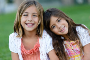 two young girls, one with pink braces, sitting in the grass
