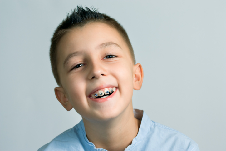 young boy wearing braces happily