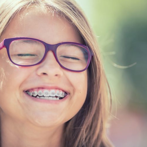 Portrait of a happy smiling teenage girl with dental braces and glasses.
