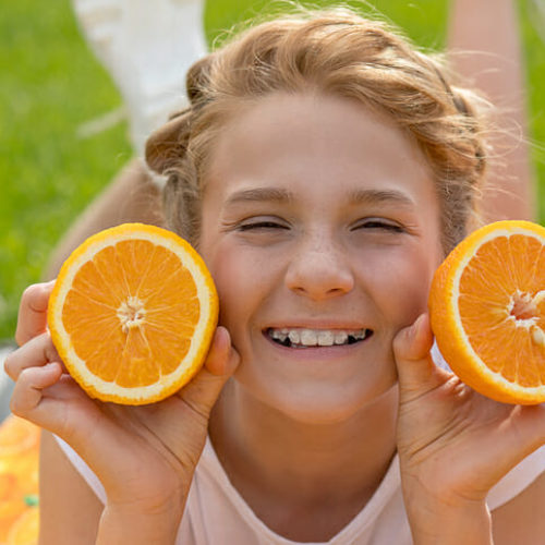Beautiful teenage girl with two oranges in her hands. She smiles broadly and laughs with ceramic braces on teeth. Not shy about them. Concept of dentistry, dental orthopedics. Healthy diet photo