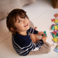 Portrait of an adorable little boy playing with colorful toy letters
